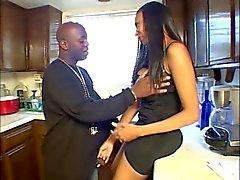 Ebony slut gives her boyfriend a blowjob in the kitchen