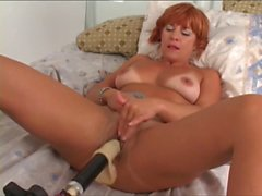 Dude slides electric dildo into bent-over b-cup redhead's pussy