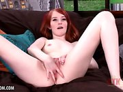 Cutie red headed co-ed strips and rubs herself on the couch
