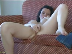 Mom alone on a hotel room couch plays with her pussy