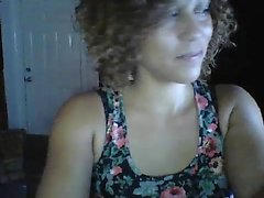 Curly haired brunette is on live cam slowly taking off her