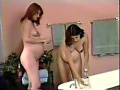 Two hot brunette pregnant lesbians take a shower together and wash tits