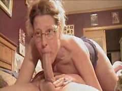 Woman in glasses deepthroats long cock