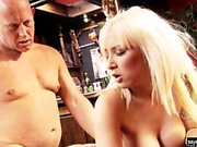 A blonde MILF with big boobs gets on her knees to suck a