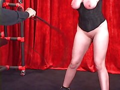 Thick sex slave with huge tits is suspended by her arms in bondage dungeon