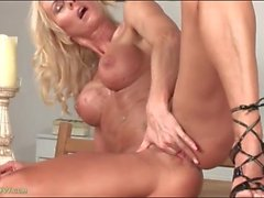 Tanned milf with beautiful fake tits fingers her cunt