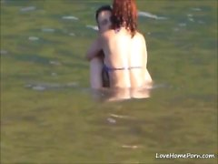 Horny couple having some fun in the water at the beach